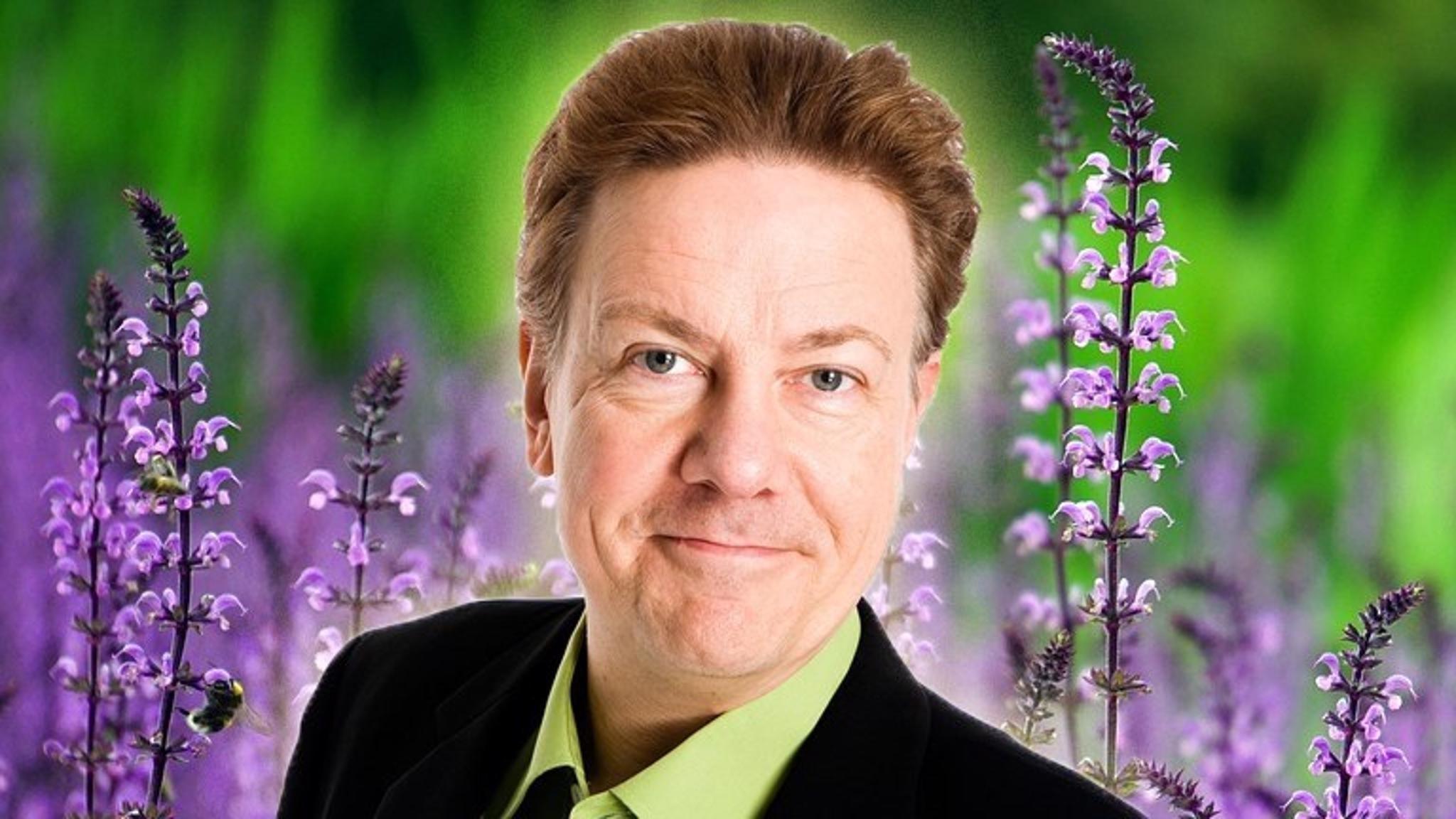 Anders Eldeman med somriga blommor i bakgrunden.
