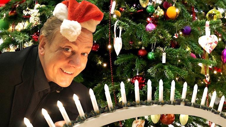 Anders Eldeman har på sig en röd tomteluva och håller i en ljusstake. Han kikar fram från höger och det är en julgran bakom honom.