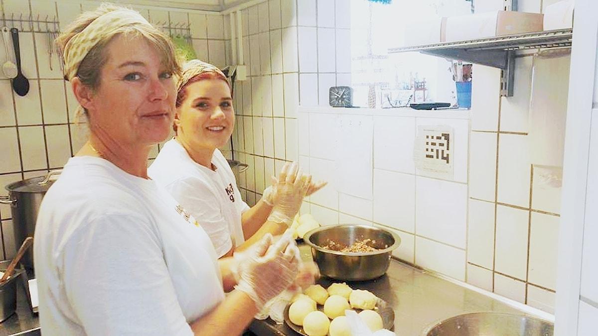 Veckans lyssnarbild kommer från Linnea Elizabeth Almgren på Kroppkakan. På bilden ser vi hur två kvinnor bakar kroppkakor och löser Melodikrysset samtidigt. De tittar in i kameran och befinner sig i ett restaurangkök där de har satt upp ett utskrivet kryss på väggen.