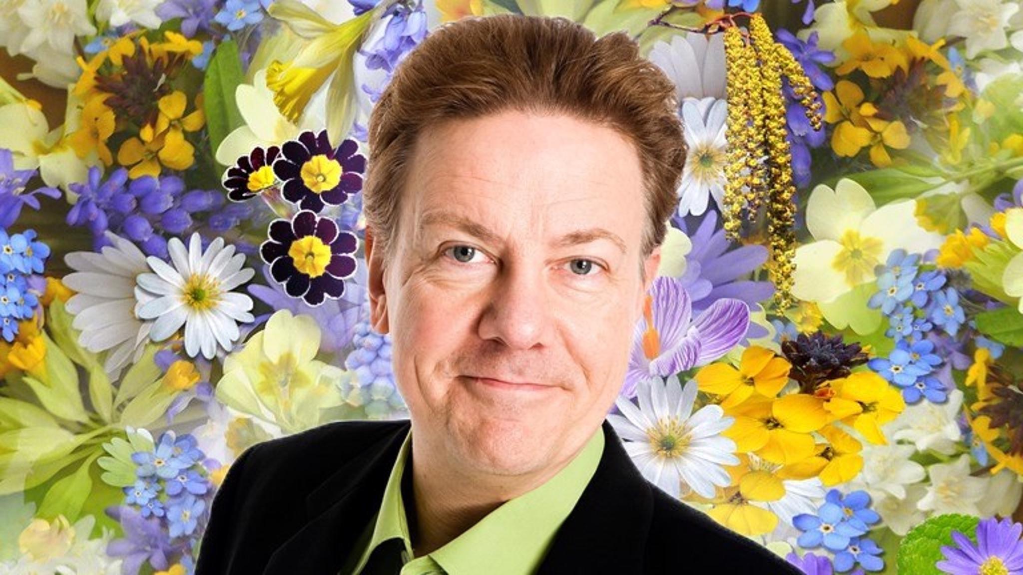 Anders Eldeman i förgrunden i bakgrunden somriga blommor.