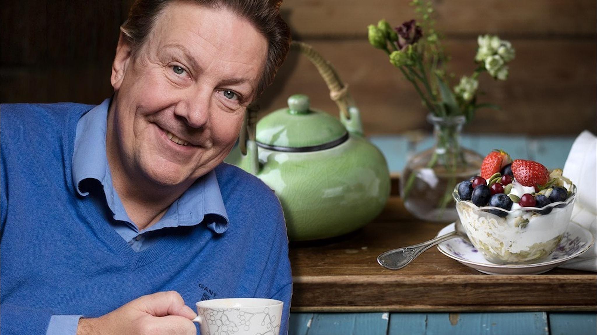 Anders Eldeman, klädd i blå tröja, med en kaffekopp och i bakgrunden en lyxig frukostbricka.