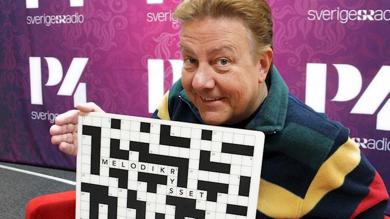 Anders Eldeman håller upp det nya priset i Melodikrysset. En skärbräda som ser ut som ett rektangulärt Melodikryss.