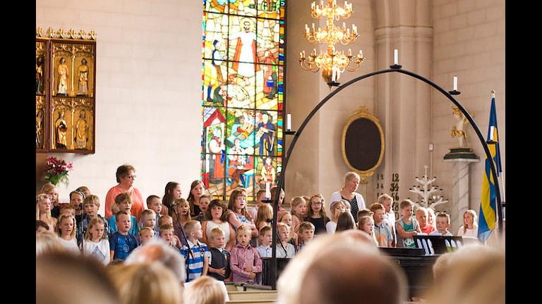 Skolavslutning. Barn och lärare sjunger i kyrkan