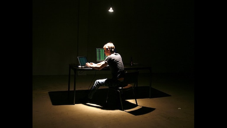 Хакер за компьютером в темноте