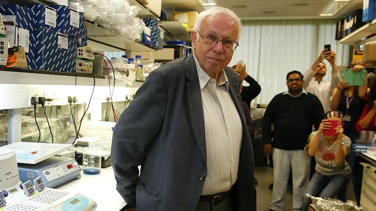 Der Schwede Tomas Lindahl ist einer der drei Preisträger des Nobelpreises in Chemie 2015. er wird in seinem Labor am Francis Crick institut in London fotografiert. Im Hintergrund halten seine Kollegen das Ereignis mit ihren Handys fest. (Foto: AP Photo/Alastair Grant)