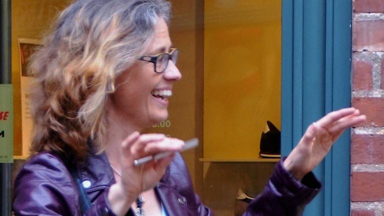 Die strahlende Chorleiterin Maria Elisson in lila Lederjacke dirigiert Köörmit bei einem Auftritt in Halmstad, Schweden (Foto: privat)