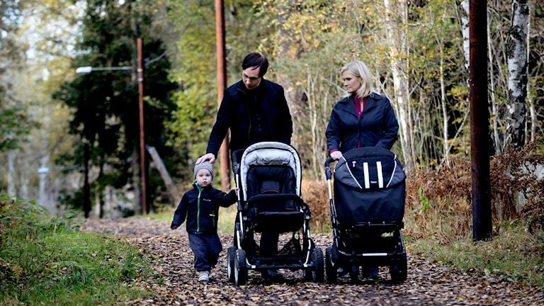Man och kvinna går med barn i skogen.