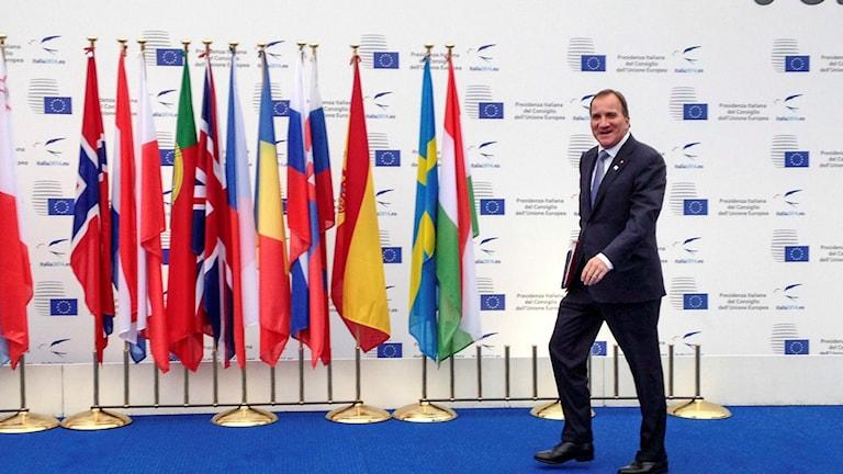 Stefan Löfven gående vid olika nations flaggor på  EU-möte