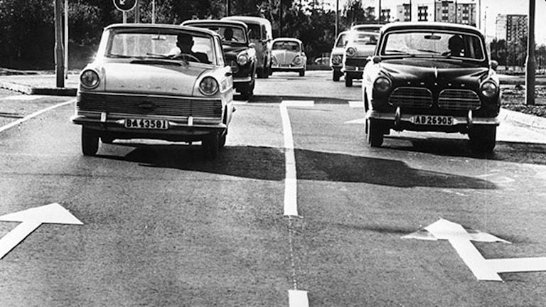 Sverige gick över från vänster- till högertrafik den 3 september 1967. Bilden är tagen i Stockholm i det ögonblick som trafikanterna försiktigt fick byta sida, klockan fem på morgonen. Ommålningen av gatumarkeringar fick ibland göras i efterhand. Därför verkar bilarna köra mot enkelriktat. Foto: TT