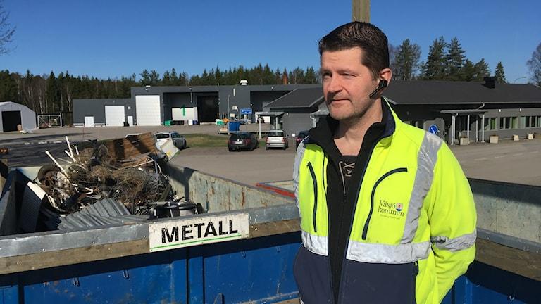 En man står franför en container med metallskrot