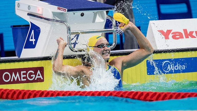 Foto av Sarah Sjöström som gör en segergest i vattnet efter att ha vunnit guld i VM.