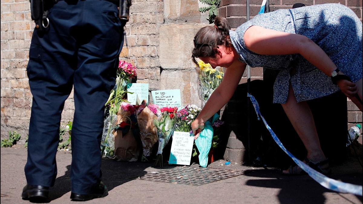 En kvinna lägger ned en blomma vid polisavspärrningarna nära platsen där nattens misstänkta terrordåd ägde rum.