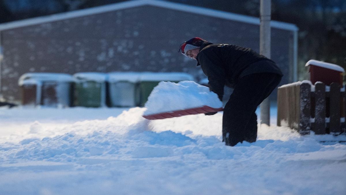 Kvinna skottar snö.