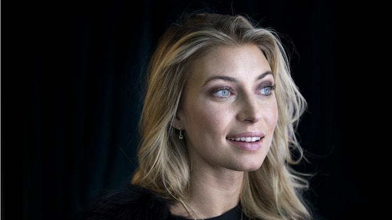 Blond kvinna i 30-årsåldern fotograferad mot svart bakgrund