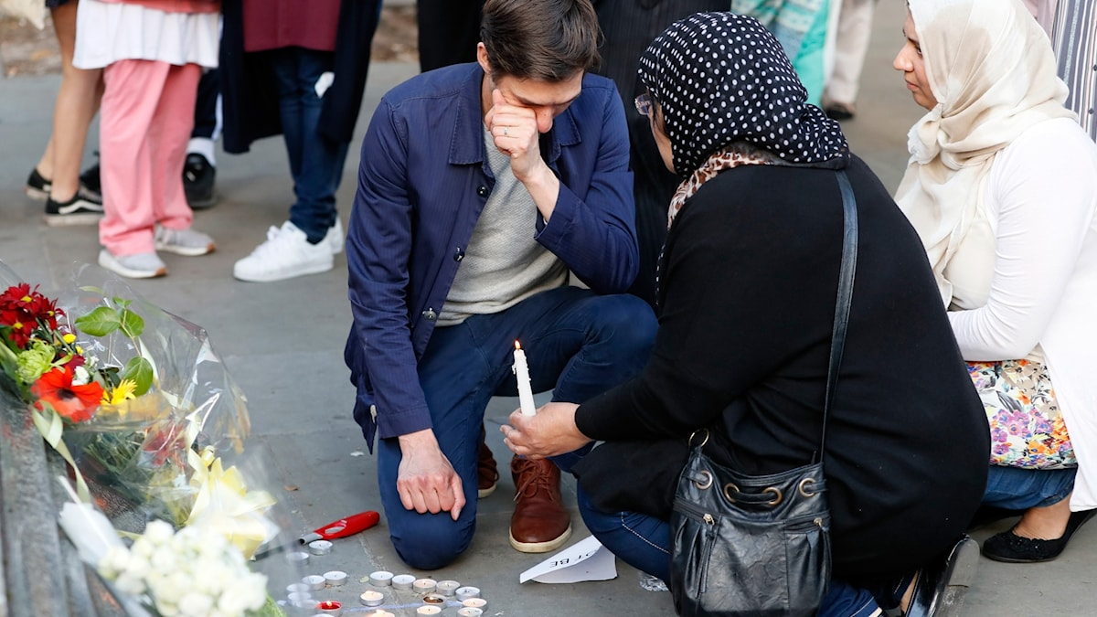 People attend a vigil in Albert Square, Manchester, England