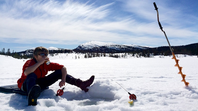 Person sitter på isen och pimplar