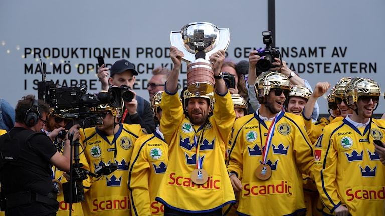 Joel Lundqvist håller upp VM-bucklan för hockeysupportrarna som samlats på Sergels torg i Stockholm för att hälsa landslaget efter VM-guldet.
