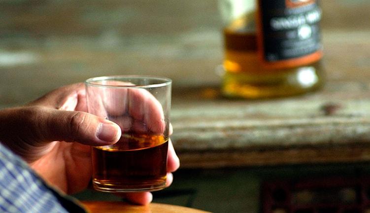 En man med ett whiskyglas i handen