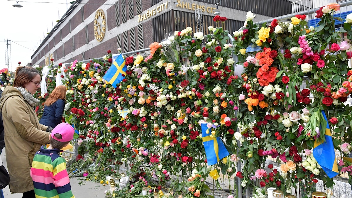 tusentals blommor upphängda på ett stängsel framför Åhléns i Stockholm
