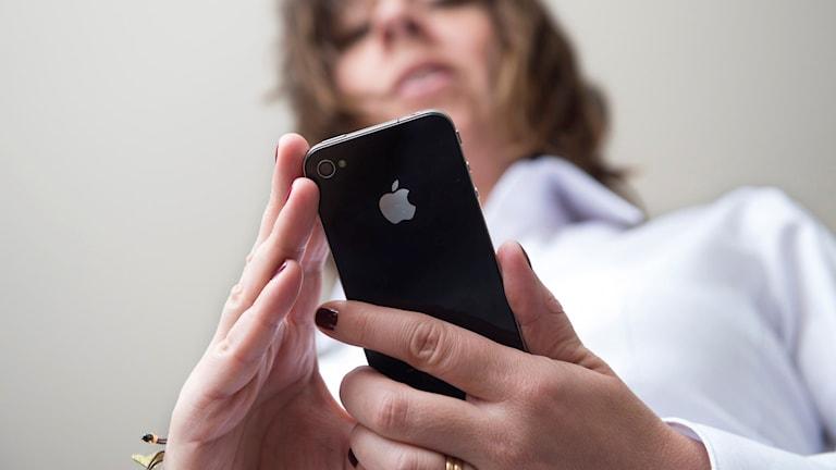 Kvinna tittar på mobiltelefon.