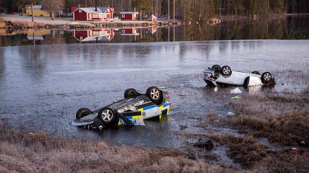 Polisbil och personbil upp och ner i vattnet. Foto: Rolf Höjer/TT