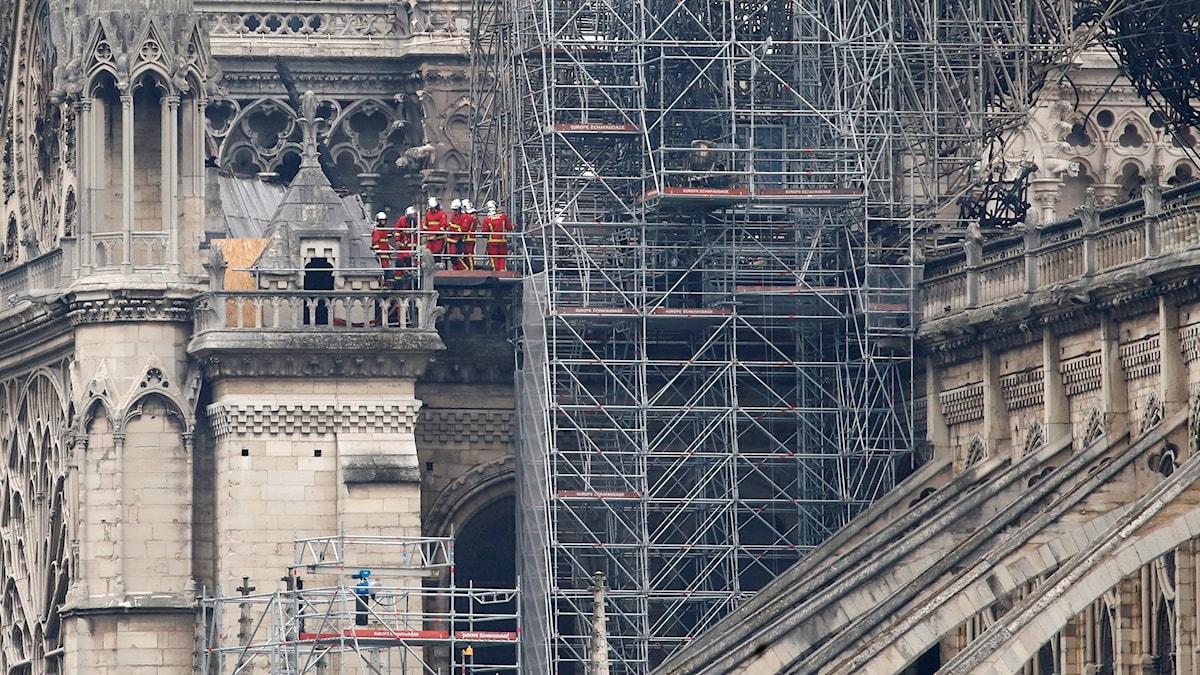 Notre Dame Katedral med brandmän som inspekterar skadorna