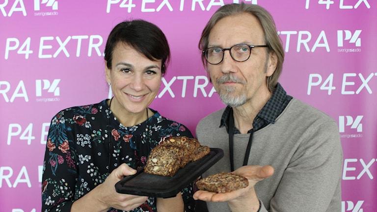 Kvinna och man ståendes framför rosa fotovägg med bröd i händerna.