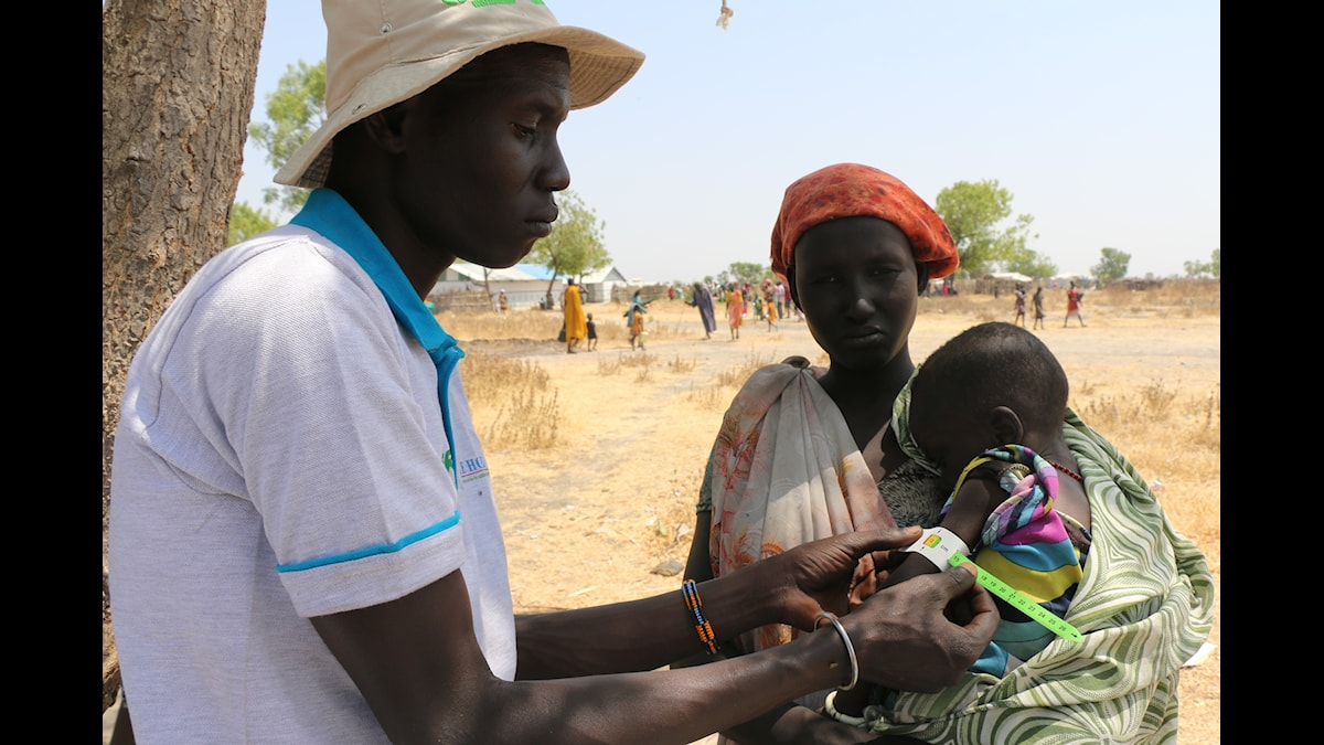 En kvinna håller ett litet barn i famnen samtidigt som en man mäter omkretsen på barnets arm.