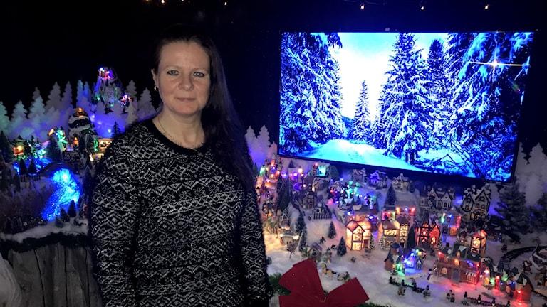 Kvinna i medelåldern i brunt hår, står framför gigantisk julby.