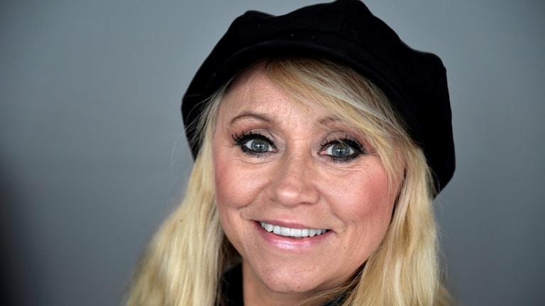 Artisten Nanne Grönvall i blont hår, svart basker och ett stort leende.