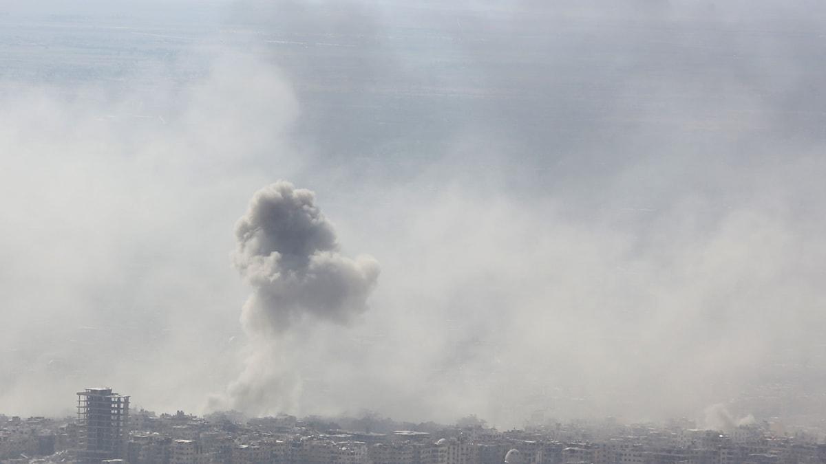En stad som delvis täcks av ett stort rökmoln.
