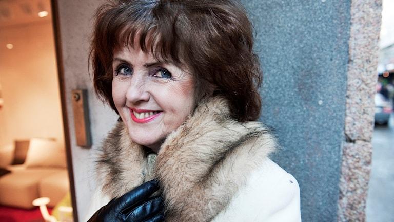 En äldre kvinna med vit kappa, svarta handskar och brunt hår ler mot kameran.