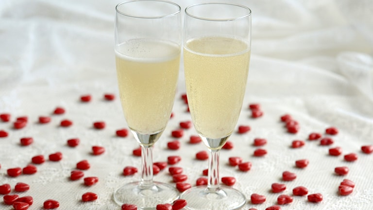 Champagneglas omgivna av små röda hjärtan.