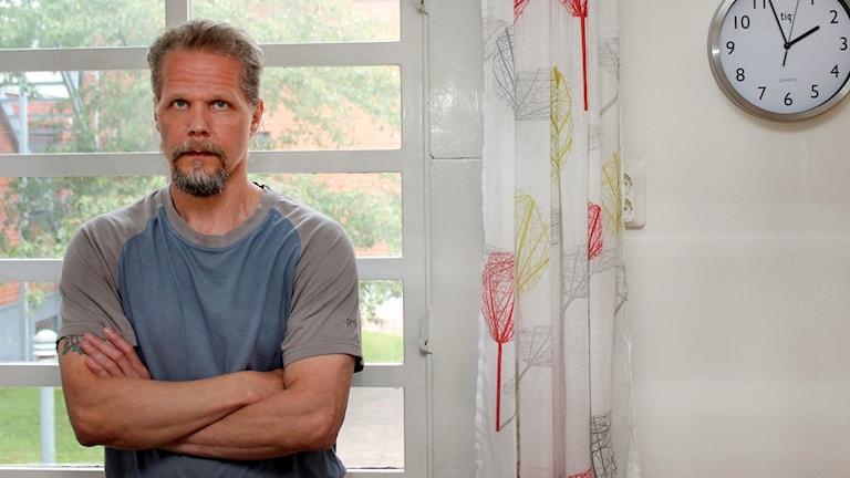 Kaj Linna, en man i blå t-shirt står med armarna i kors framför ett fönster.