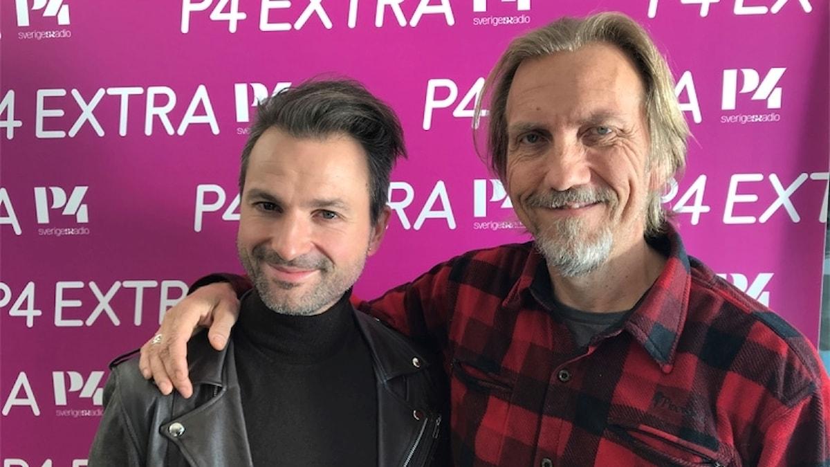 Artisten Ola Salo och programledare Erik Blix framför fotovägg.