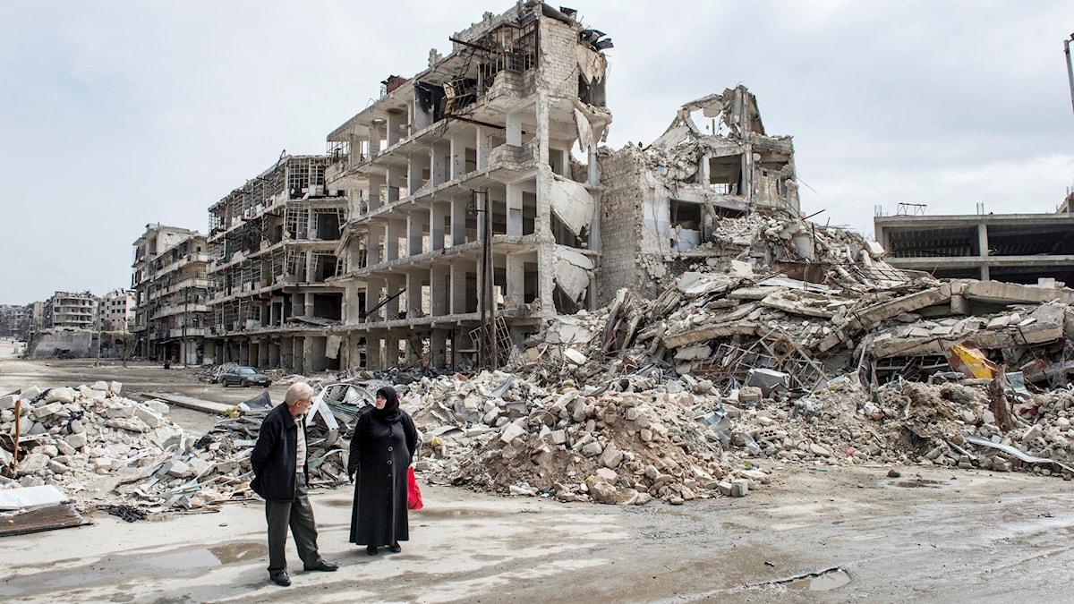 En man och en kvinna stående vid ett krigsförstört hus i östra Aleppo i Syrien.