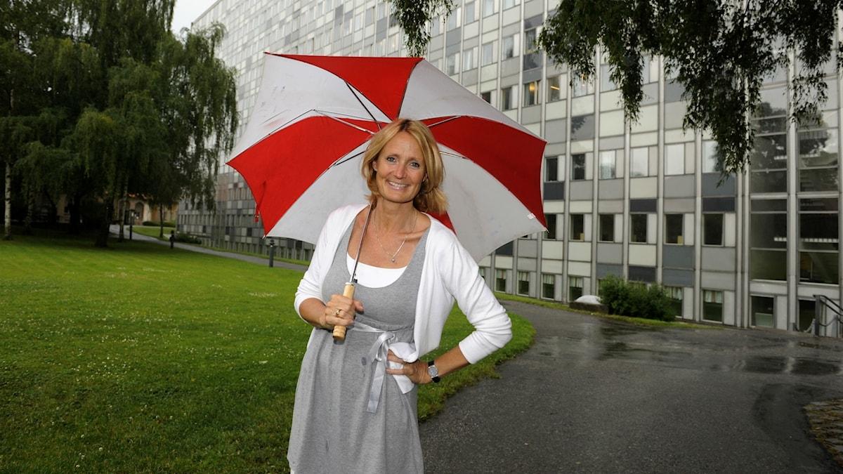 Bibi Rödöö med uppslaget paraply utanför Radiohuset.