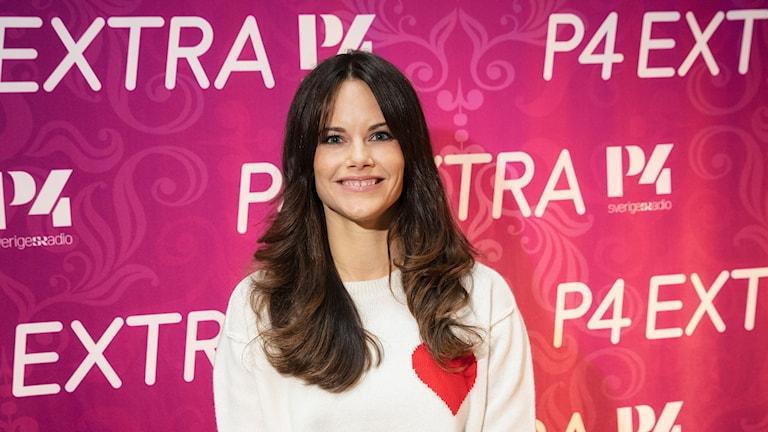 Prinsessan Sofia ståendes framför rosafotovägg. Prinsessan bär en vit tröja med ett rött hjärta tryckt på tröjan.