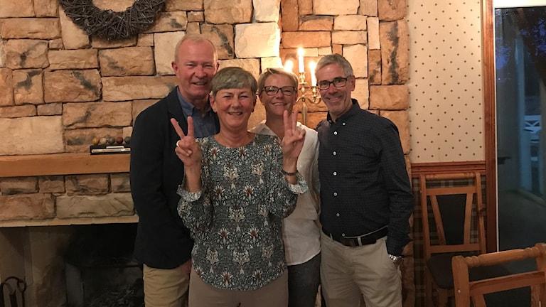 Fyra glada personer varav en står framför och gör v-tecken.