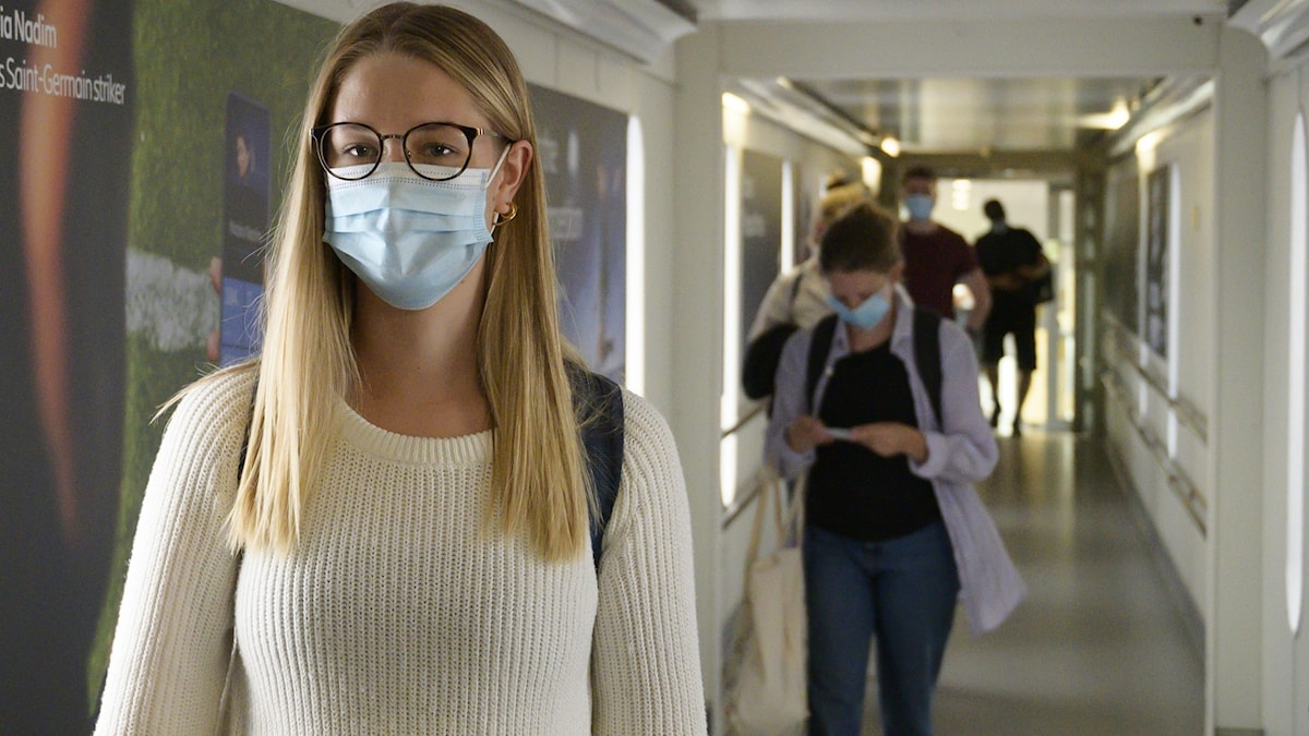 Kvinna i en korridor med munskydd