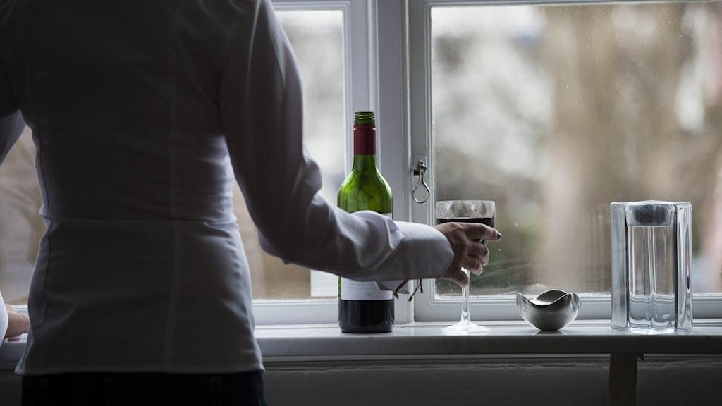 Kvinna står vid fönster och dricker vin.