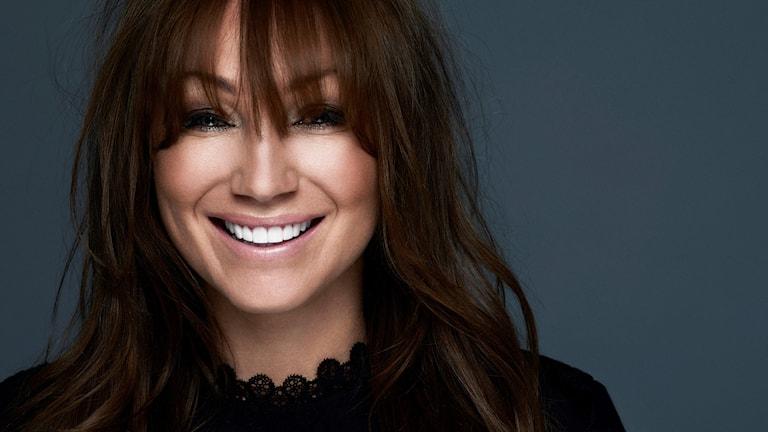 Kvinna, ler, lång lugg som hänger fram i ansitket. ståendes framför gråblå vägg