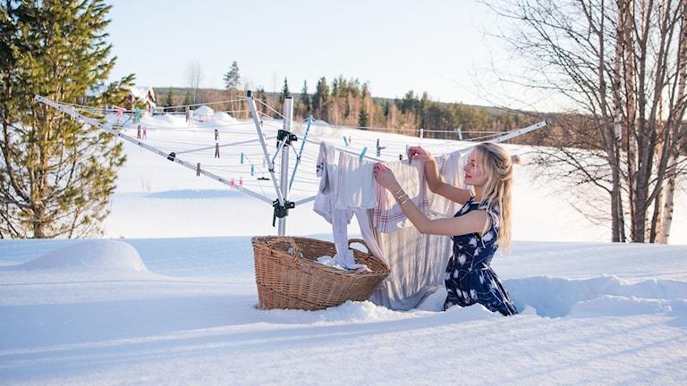 Jonna Jinton hänger tvätt i meterhög snö.