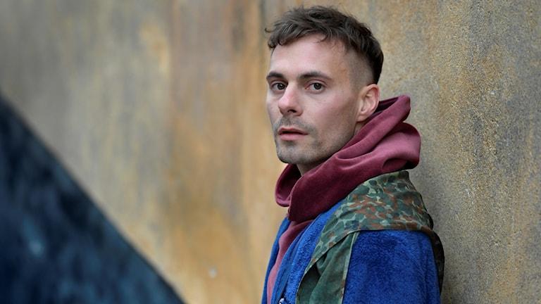 Oskar Linnros står lutad mot en vägg.