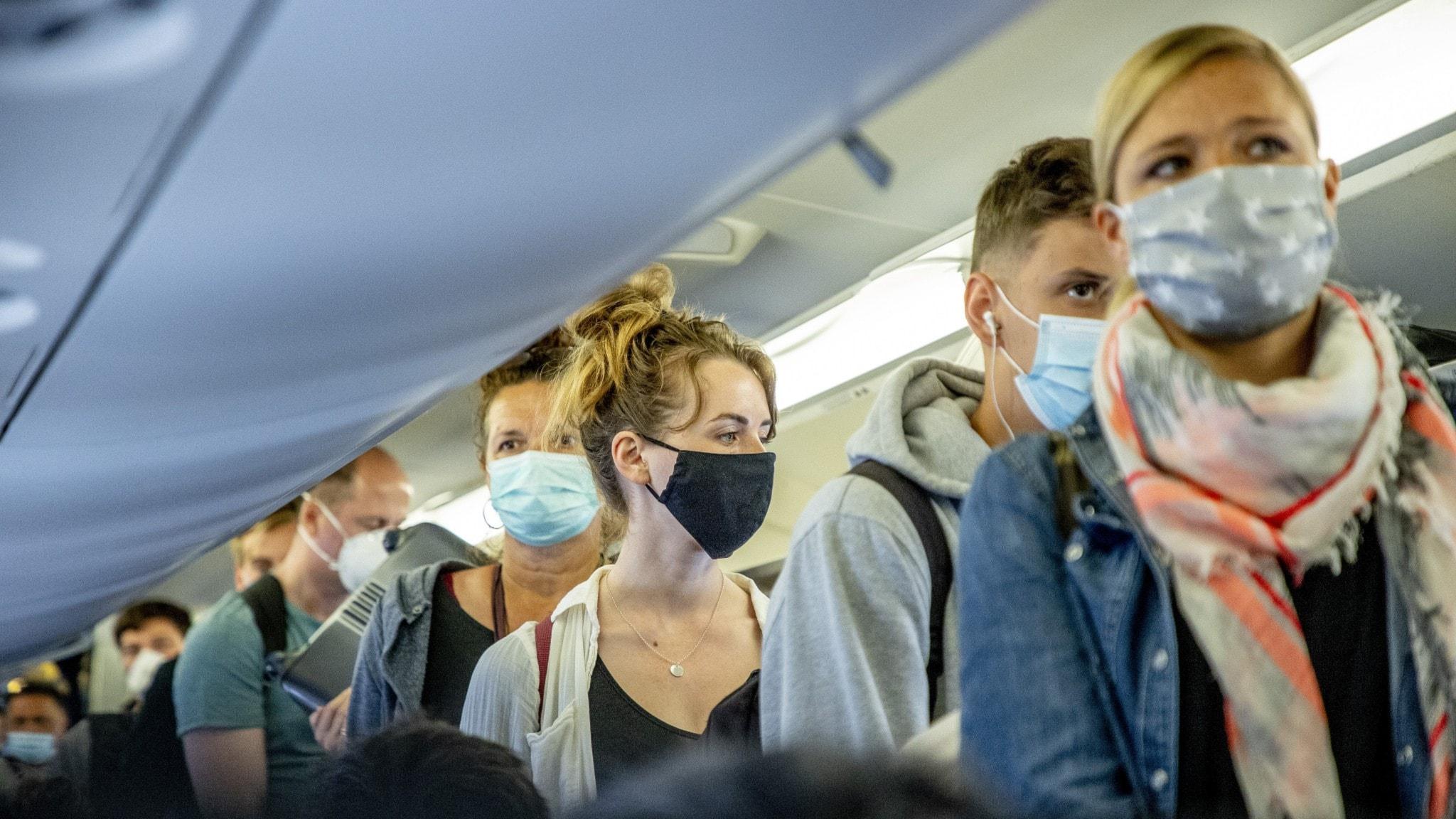 Resenärer med munskydd på plan.