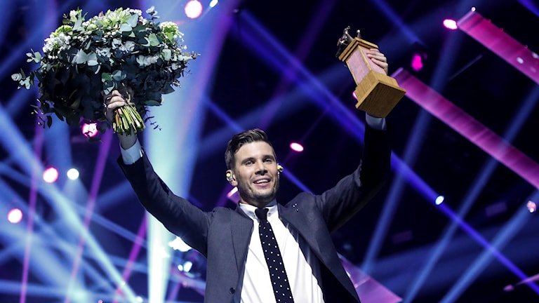 En glad Robin Bengtsson med blommor och vinnarpokalen.
