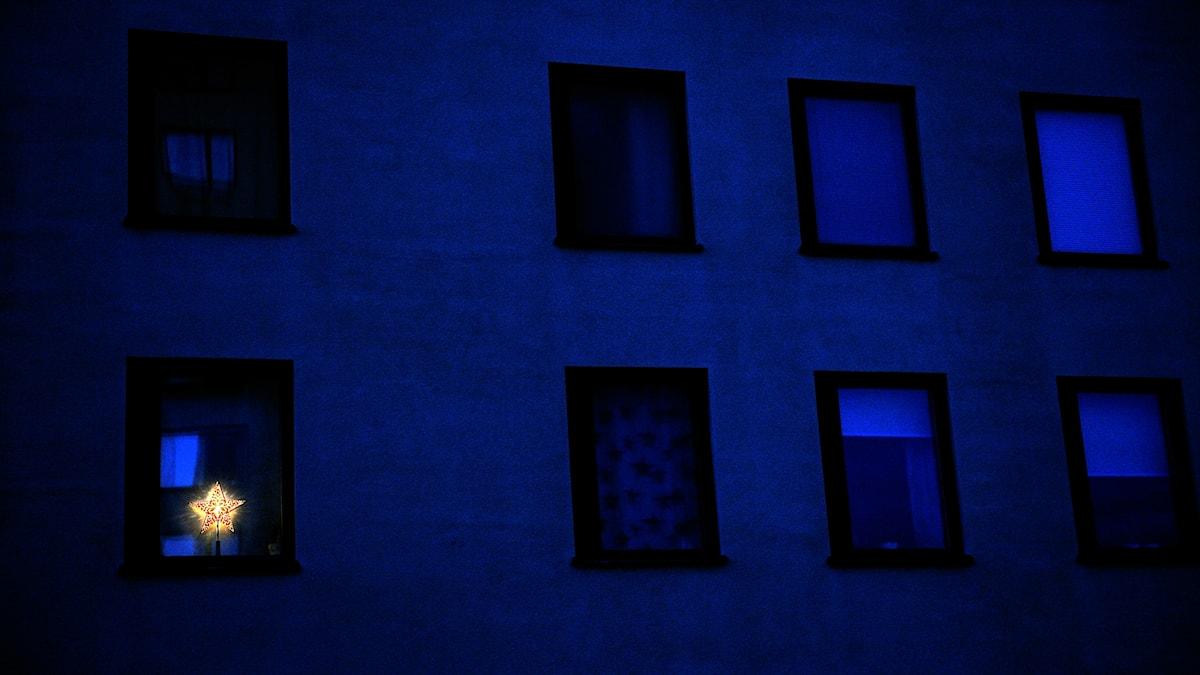 En adventsstjärna i ett fönster. Ljus i mörker.