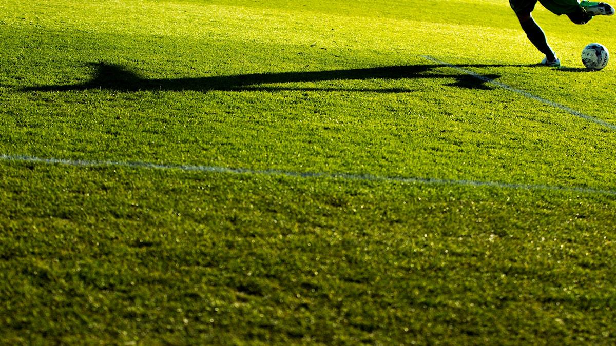 En stor fotbollsplan där man ser två ben sparka på en boll.