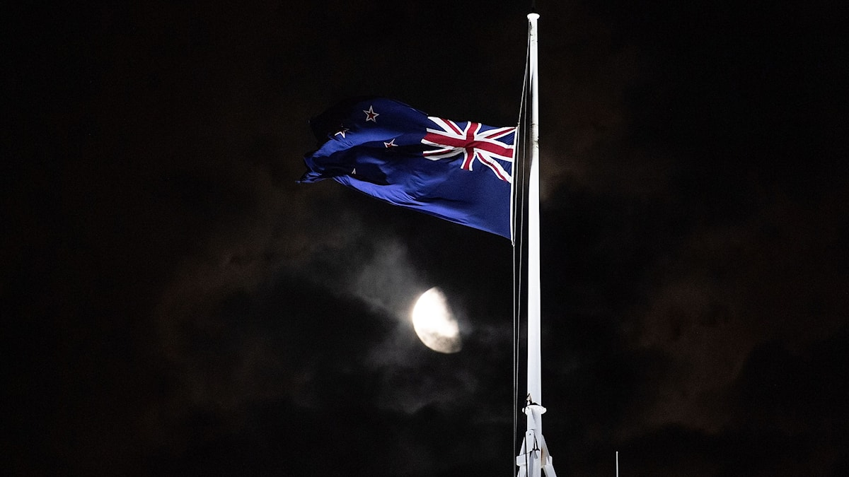 Nya Zeelands flagga på halvstång med fullmånen i bakgrunden