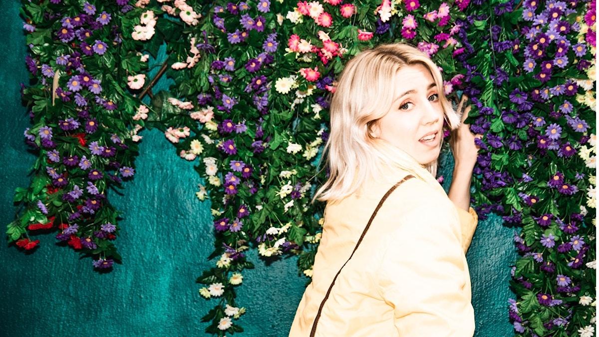 Veronica Maggio vid en vägg klädd med plastblommor.
